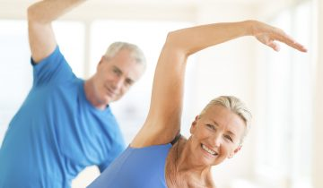 Portrait of smiling senior couple performing stretching exercise at home
